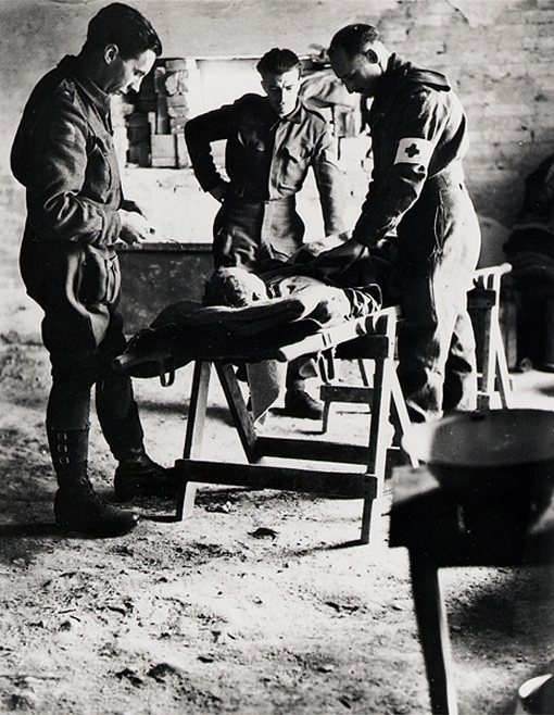 Major P.K. Tisdale, 4th Field Ambulance, R.C.A.M.C., checking the condition of a wounded man before Sergeant W.H. Brigham and Private L.P. Lemieux donate blood before his transfer to a Field Surgical Unit. Ortona, Italy, 15 January 1944.