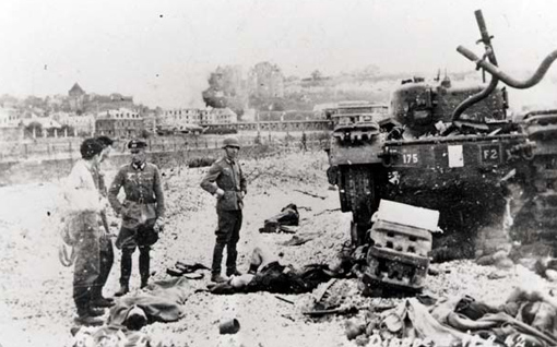 Officer and soldiers examining a Churchill tank stuck on the beach in front of the boardwalk after the battle, its left track broken. Wounded men lying on the ground are about to be evacuated. Dieppe, August 19th, 1942.