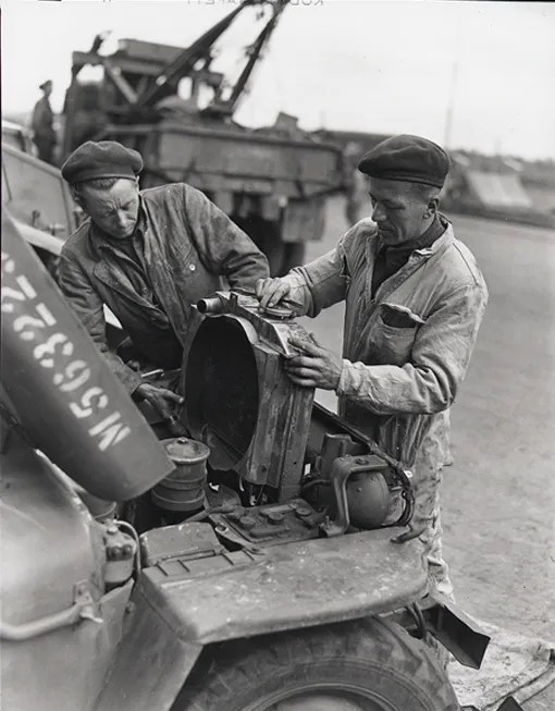 Two mechanics of the Royal Canadian Electrical and Mechanical Engineers, L.A. Einarson of Lundar, Manitoba, and Richard Donovan of Limoilou, Québec, replacing a jeep radiator after overhauling the motor.
