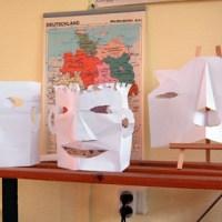 des têtes en papier plié et découpé
