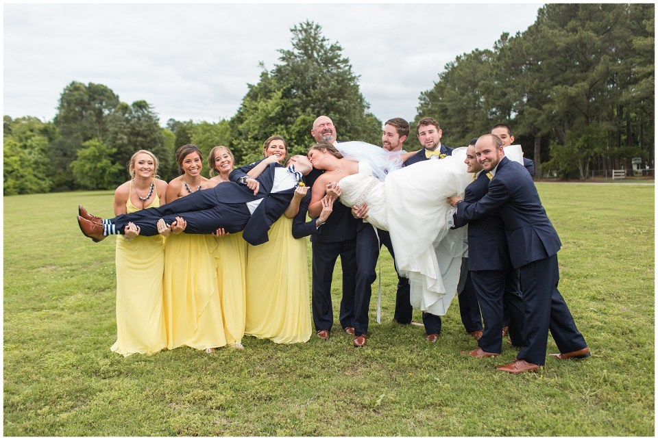 bridal party holding bride and groom