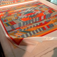 In preparation for printing, the silk for the scarves is rolled out and affixed to a waxed board.
