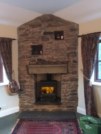 Woodwarm stove in a traditional stone fireplace wood