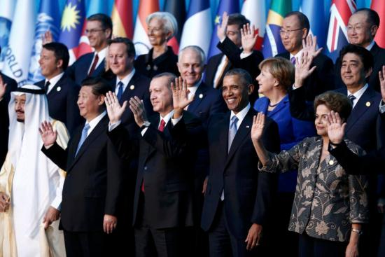 Members of the Group of 20 (G20) wave during the traditional family photo at the G20 leaders summit in the Mediterranean resort city of Antalya, Turkey, November 15, 2015. REUTERS//Aykut Unlupinar/Pool