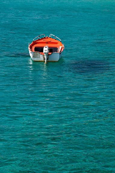 orange boat on blue-green water