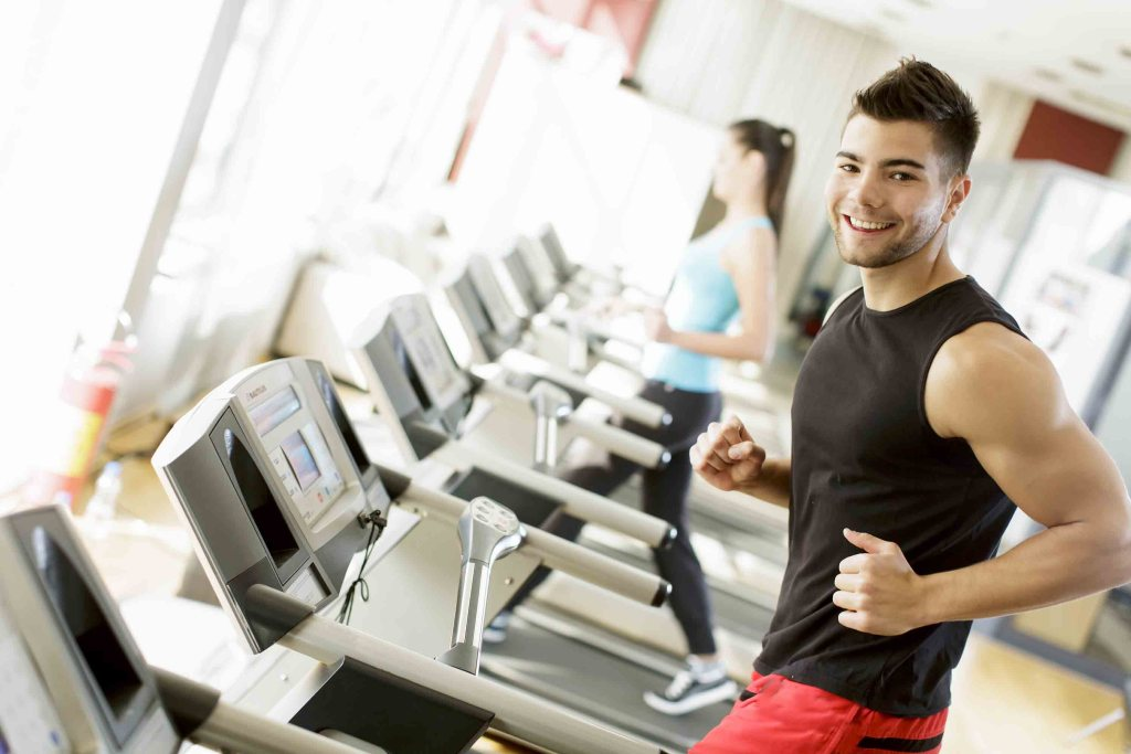 Young man running on a treadmill at the gym