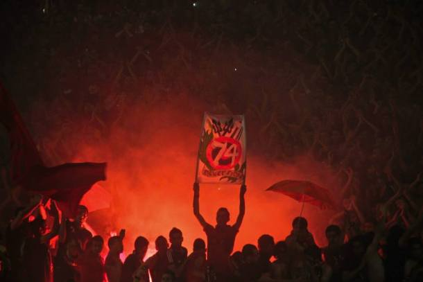 An Ahly fan with a 74 martyrs banner