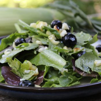 grilled corn and fresh blueberries with greens