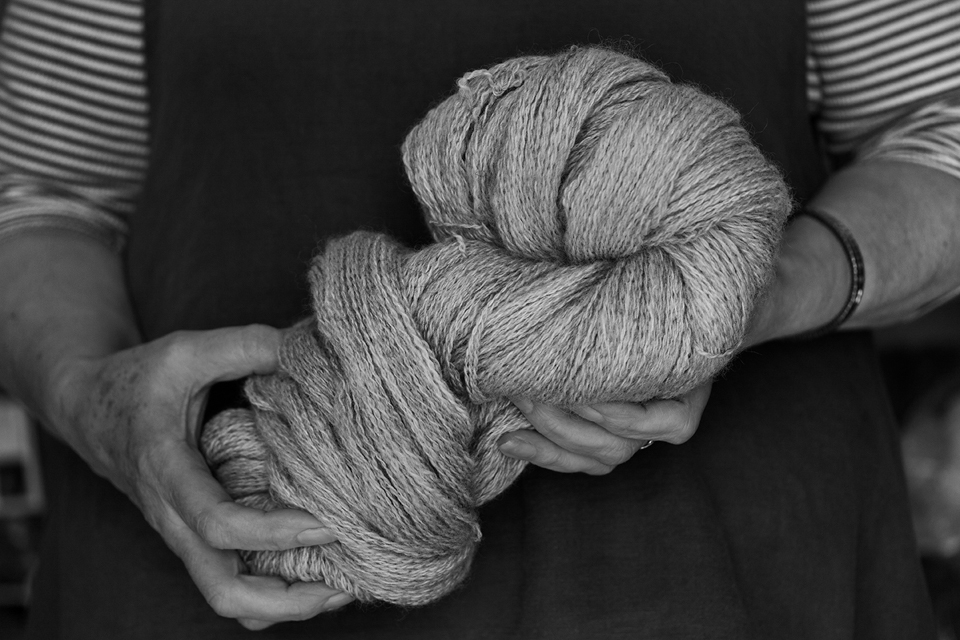 Elizabeth Johnston holding a beautiful skein of her own handspun yarn - photo © Tom Barr and used with kind permission