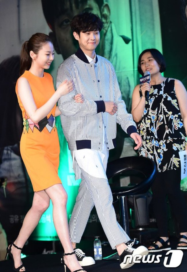 Image: Sohee holds directly to Choi Woo Sik's arm as they walk up stage together