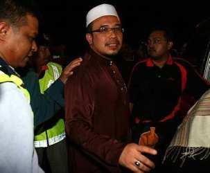 Dr Asri diiringi oleh polis ketika dibawa ke balai polis Hulu Kelang - gambar Mstar
