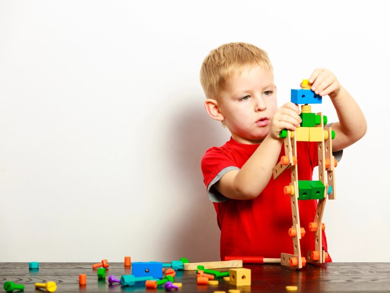 Little blond boy child kid preschooler playing with colorful building blocks toys interior. At home. Childhood and development.