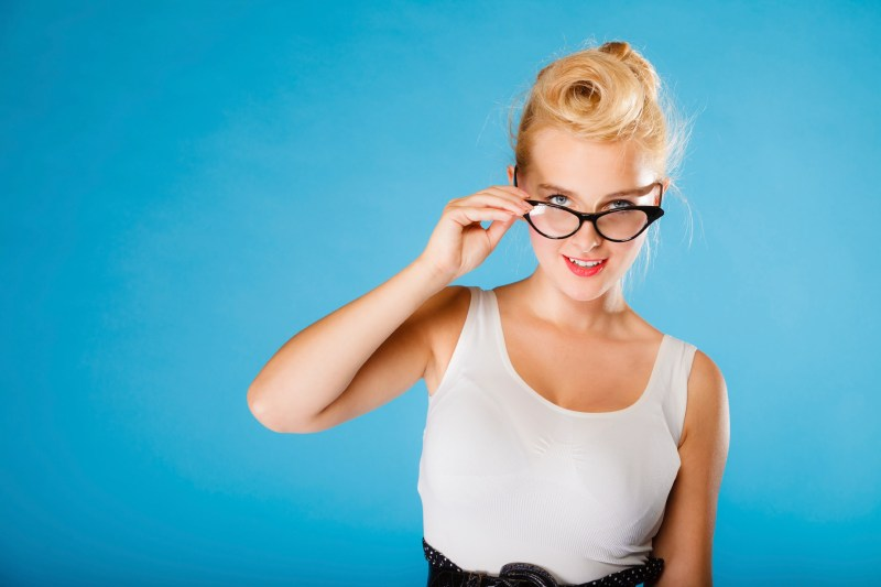 Optometrist, oculist and ophthalmologist concept. Young blonde retro pin up smiling woman with eyeglasses on blue background in studio.
