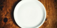 Empty white dinner plate on rustic wooden kitchen table, top view