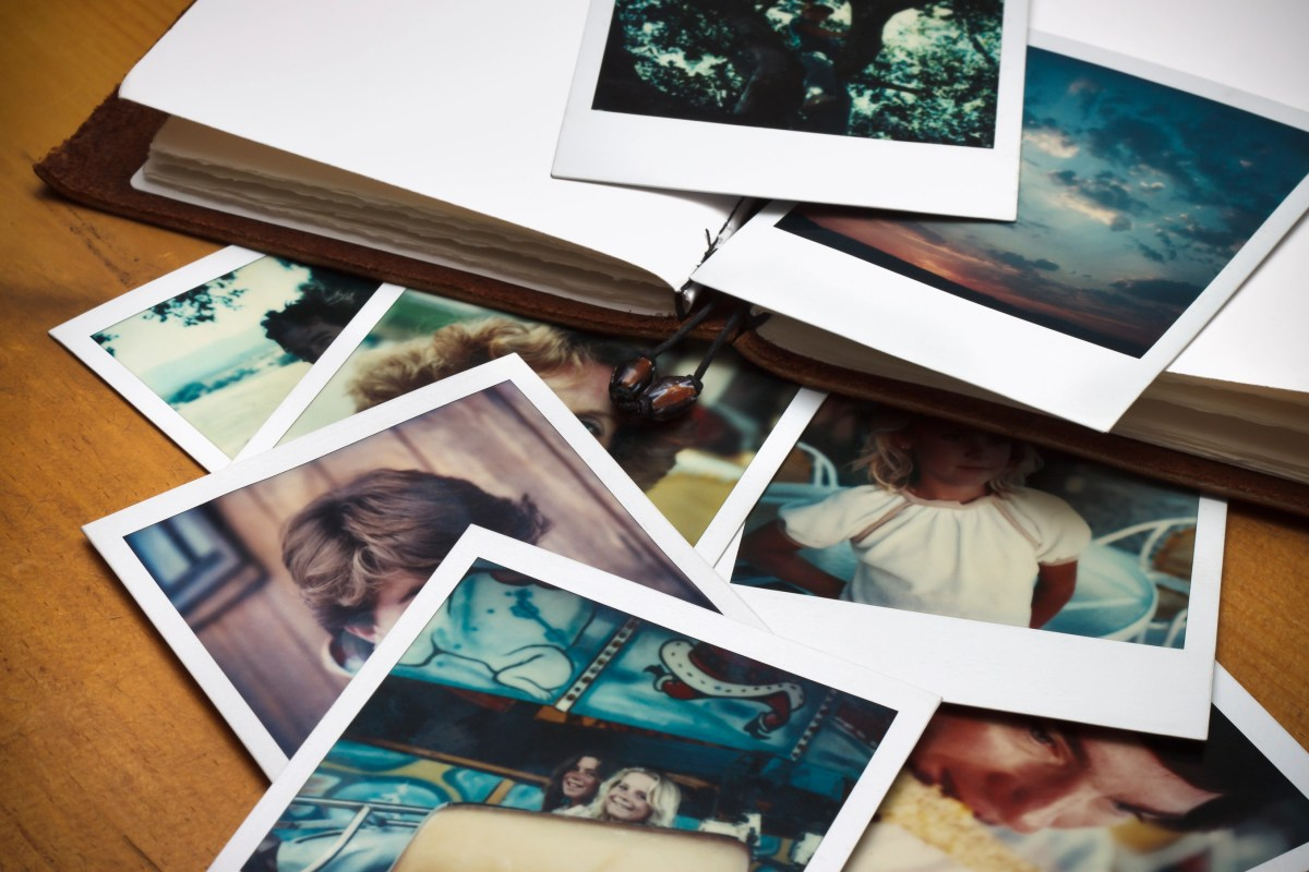 A pile of old pictures and a journal to document memories of past times.