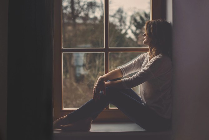Young attractive woman, sitting on a window, looking outside, lonely mood
