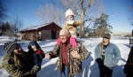 LaVoy Finicum, center, a rancher from Arizona who is part of an armed group occupying the Malheur National Wildlife Refuge to protest federal land management policies, carries his granddaughter Payton, as other family member watch following a news conference at the refuge Friday, Jan. 8, 2016, near Burns, Ore. Ammon Bundy, the leader of the group said Friday he and his followers are not ready to leave even though the sheriff and many locals say the group has overstayed their welcome.  (AP Photo/Rick Bowmer)