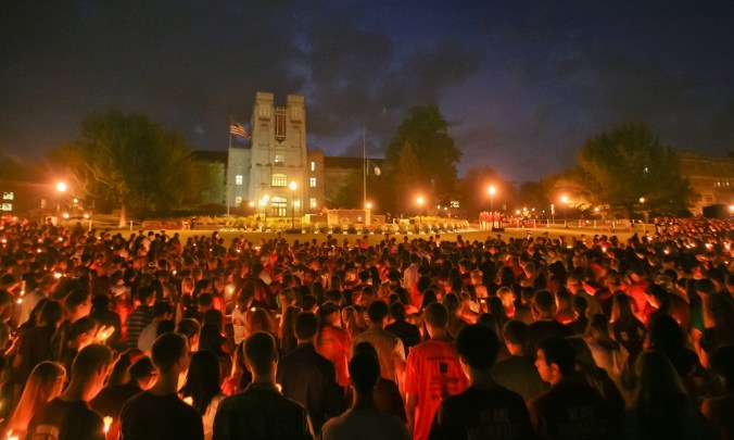 Virginia Tech students pass the flame of a memorial candle