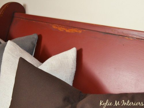 close up of painted wood church pew with red paint in Behr ultra.  This photo shows the distressed details