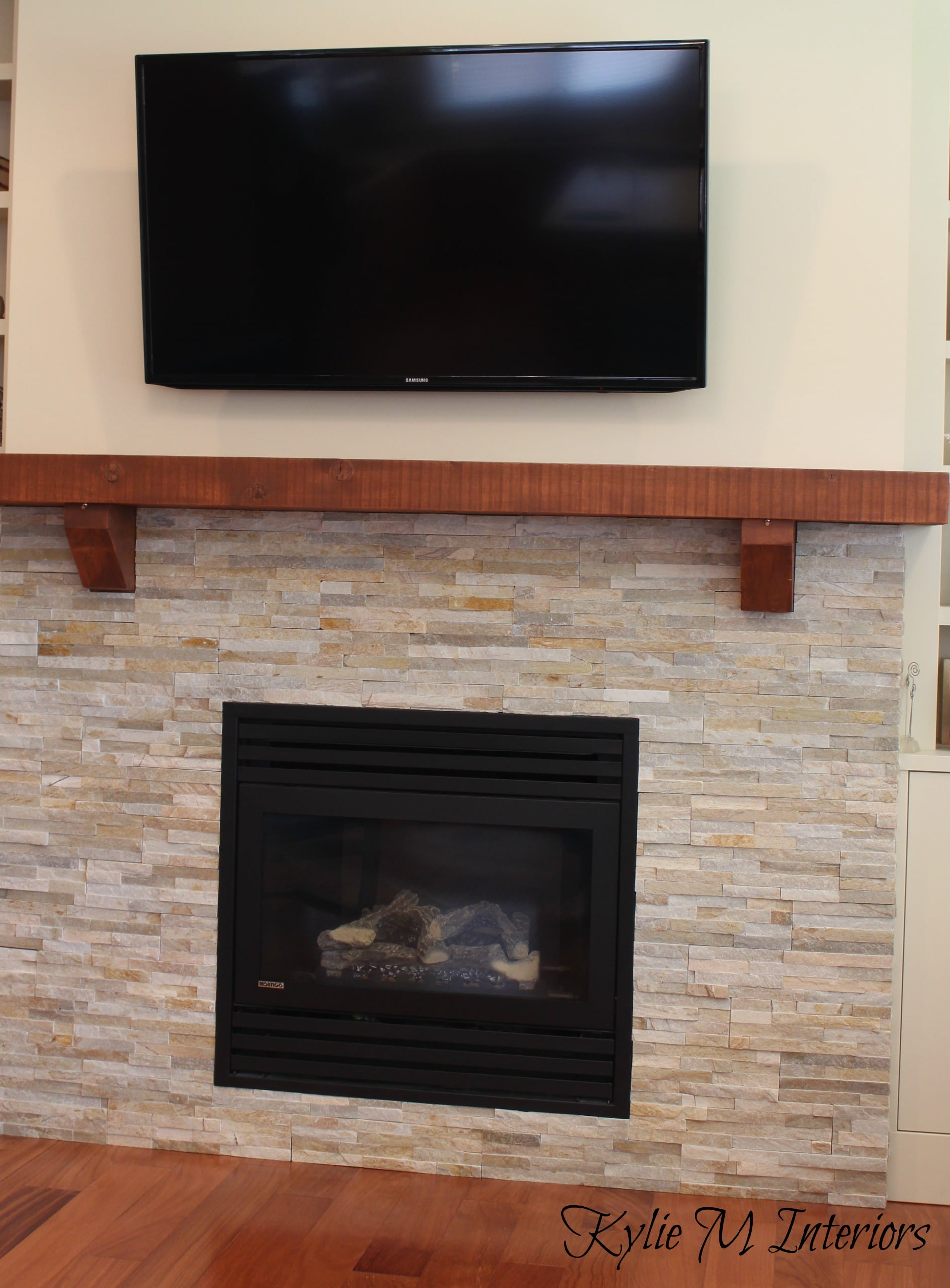 fireplace with wall mount tv earth tone stone surround