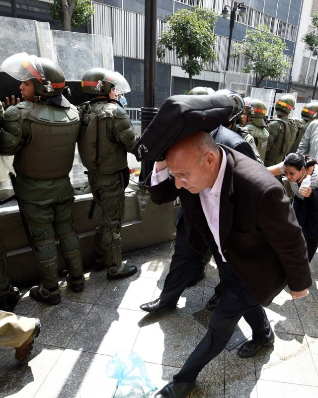 """Opposition lawmakers protect themselves while they try to reach the National Assembly in Caracas on October 27, 2016. """"We are going to notify Nicolas Maduro that the Venezuelan people declare he has abandoned his post,"""" the speaker of the National Assembly, Henry Ramos Allup, said to cheers from hordes of protesters in Caracas. / AFP PHOTO / JUAN BARRETO"""