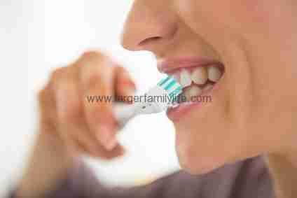 Closeup on young woman brushing teeth