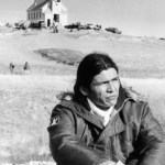 Dennis Banks, one of the AIM leaders of the Oglala Sioux Indians, sits in the open prairie on March 4, 1973 at Wounded Knee, S.D, USA, and reflects on events of the past week. The church where hostages held for a while is in the background. (AP Photo/Pool)