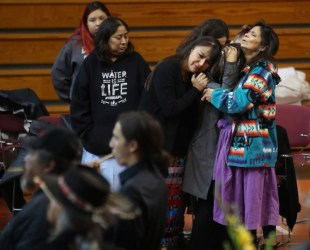 """All the family who were present prayed over him and said our individual goodbyes,"" the family said. ""Then we proudly sang him the AIM song as his final send off."" Family members console each other during an all-night visitation for Dennis Banks, who helped found the American Indian Movement, at the American Indian Center, Wednesday, Nov. 1, 2017 in Minneapolis, Minn. Banks died at age 80, his family announced Monday. (Jerry Holt/Star Tribune via AP)"