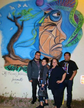 Jay Michael Jaramillo (left) with friends & family stands in front of his art work at Su Teatro. The art is also part of the feature film ROOT by Molina Speaks.