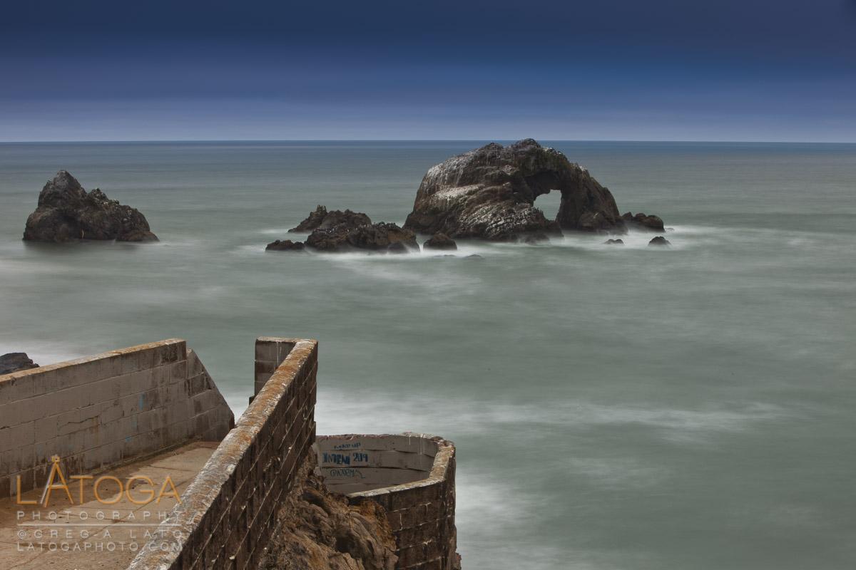Seawall reaches out toward Seal Rocks during Dusk at Sutro Baths in San Francisco, California.