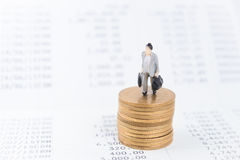 Mini person standing on stack of coins.