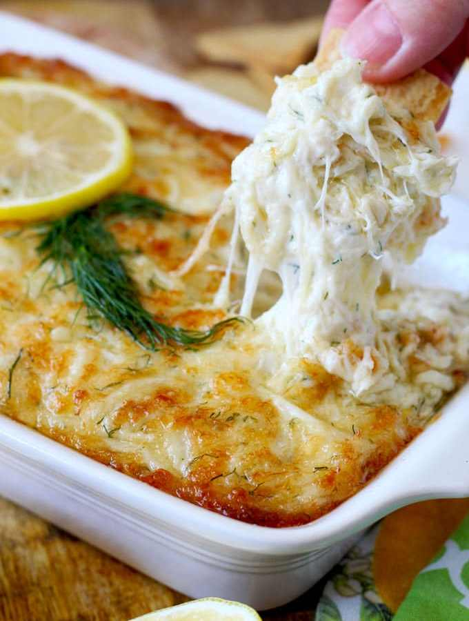 Lump crab meat, cheese, lemon and dill are baked to bubbly and gooey golden brown perfection. This Hot and Cheesy Crab Dip is scrumptious, rich, delicious and the ultimate party dip!