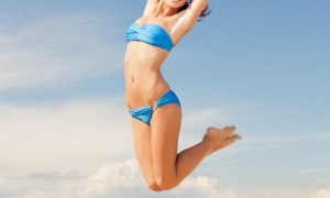 bright picture of happy jumping woman on the beach.