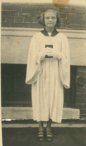 "Virginia Farley Mazzenga, avid fan of Bishop Fulton Sheen, in her confirmation robe, ca. 1953. An avid follower of Sheen's Life is Worth Living at the time, she says when she watched him on TV it was ""as if nothing else was happening in the room. The way he was able to put the teaching over was out of this world."""