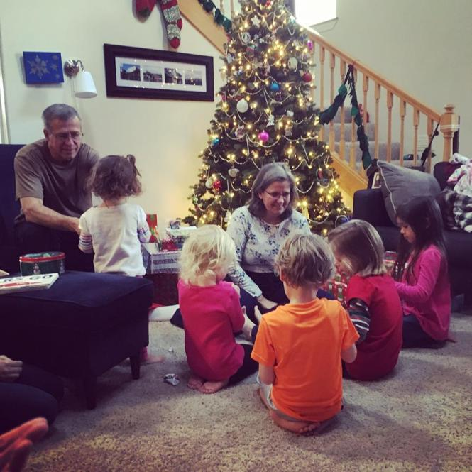 Grandparents opening presents with some of the grandkids