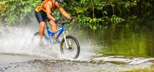 26 Sep 2013, Wailua, Kauai, Hawaii, USA --- Speeding mountain biker splashing through a stream, Kauai, Hawaii --- Image by © Mark A. Johnson/Corbis