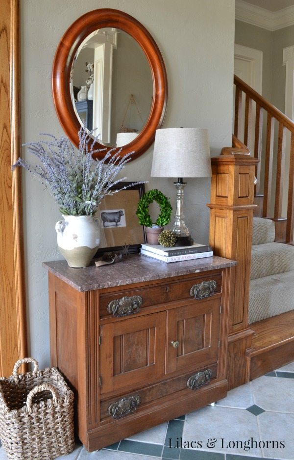 An antique marble top chest fits perfectly on this small wall.