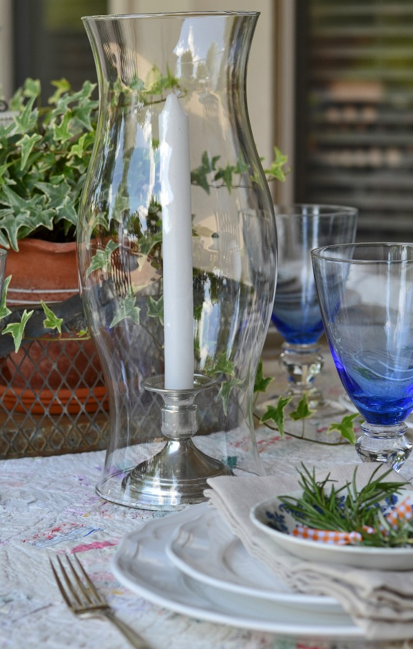 glass hurricane and silver candle sticks