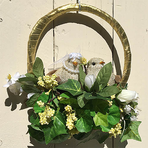 Small wreath with upcycled flowers and foliage and purchased lovebird ornaments.