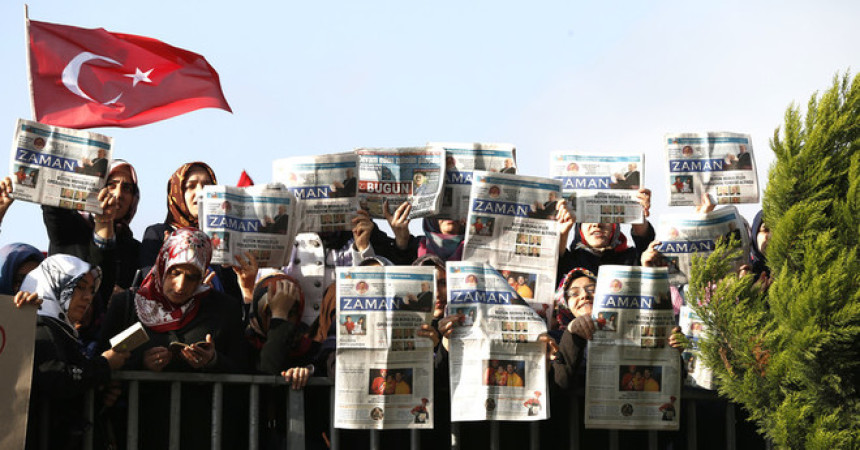 epa04528897 Supporters of Fethullah Gulen Movement shout slogans and hold copies of the Zaman newspaper as they take part in a demonstration outside a courthouse after Turkish police began an operation targeting the media close to the Fethullah Gülen, in Istanbul, Turkey 14 December 2014.Early 14 December police simultaneously arrested broadcasters from a television station and a former anti-terrorism chief and journalists according to local media.  EPA/TOLGA BOZOGLU