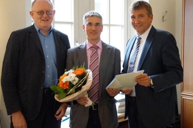 Technischer Beigeordneter Thorsten Paulussen (Mitte) erhält aus den Händen von Bürgermeis- ter Christian Liebrecht (rechts) im Beisein des Personalratsvorsitzenden Rüdiger Fuhrmann (links) die Ernennungsurkunde für seine zweite Amtszeit als Beigeordneter der Stadt Lage.