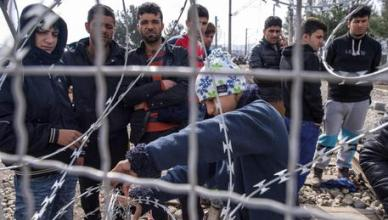 Refugees wait on the Greek side of the border to cross in Macedonia