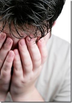 sad teenage boy with head in hands