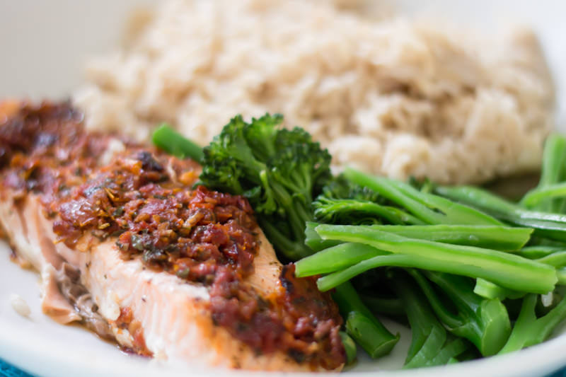 Salmon with a sun dried tomato topping, greens and brown rice