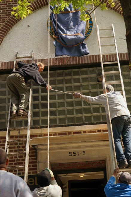 Silas and Ray pass a tool between two ladders