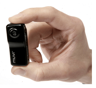 Veho Muvi helmet camera held by a hand to show how small it is