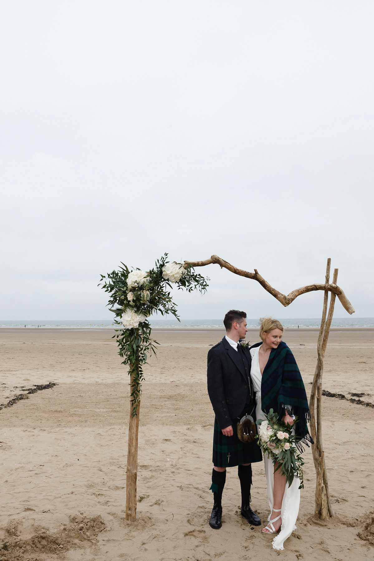 Laura wears a 1970's inspired Stone Cold Fox wedding dress for her laid back and organic beach wedding in Scotland. Photography by Tino and Pip.