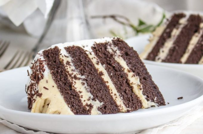 A slice of low carb chocolate layer cake filled with vanilla pudding, on a plate.