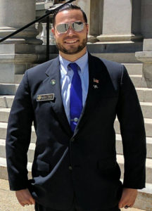 Brandon Phinney (NH rep) standing in front of legislative building in New Hampshire, wearing suit, tie, sunglasses, name badge, American flag lapel pin