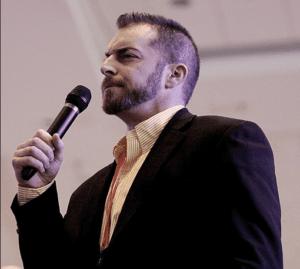 Adam Kokesh speaking at a mic wearing dark blazer, open-collar shirt (color photo)